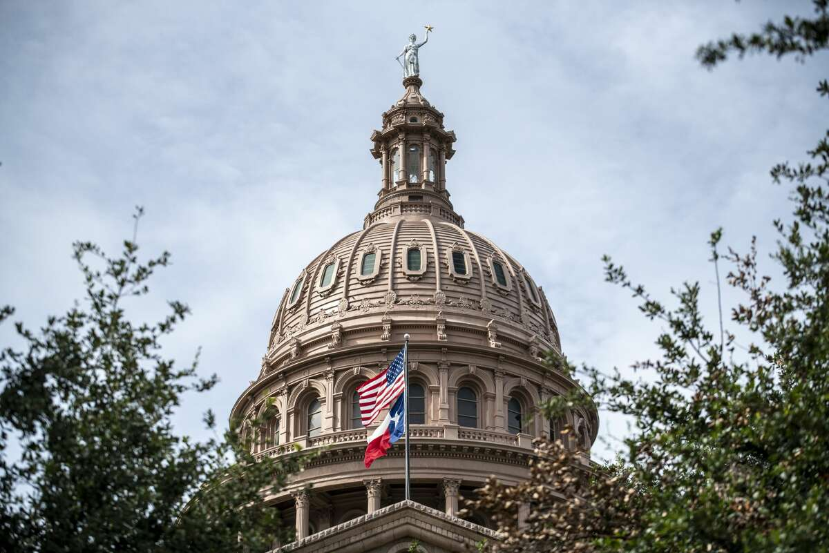 AUSTIN, TX - JULY 12: The U.S. and Texas state flags fly outside the state Capitol building on July 12, 2021 in Austin, Texas. Texas Democrats have fled the state in order to prevent a quorum in protest over a Republican voting protection bill that they say is too restrictive. (Photo by Sergio Flores/Getty Images)