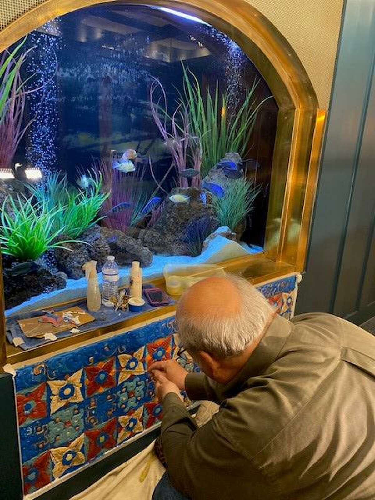 John Coutu touches up the tiles around the aquarium in the lobby of the Majestic Theatre.