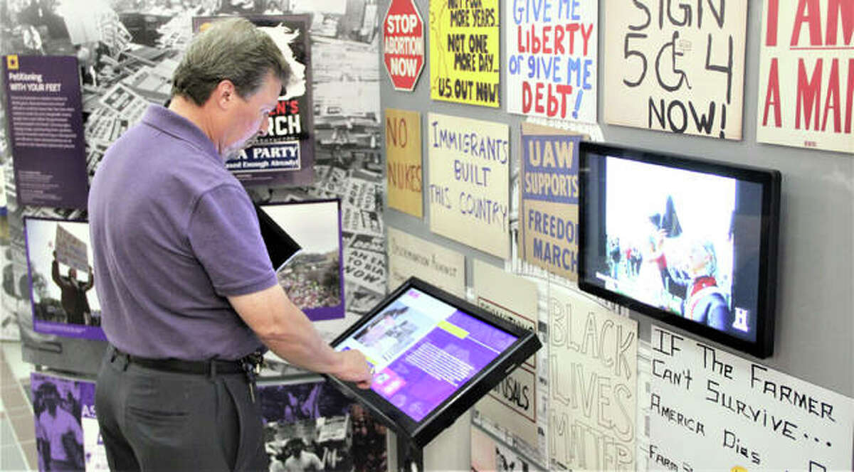 """Loftin Woodiel, of Rosewood Heights, looks over some of the interactive features making up """"Voices and Votes: Democracy in America,"""" part of the Smithsonian's """"Museum on Main Streets"""" program, that runs July 19 through Aug. 20 in the Madison County Administration Building. Woodiel was being trained Thursday as a volunteer docent, or tour guide, for the exhibit."""