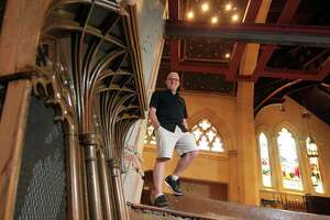 Christ Church of Greenwich Director of Music Jamie Hitel poses at the church in Greenwich, Conn., on Wednesday July 14, 2021. The church cleared out their old organ and are doing extensive construction on the space in anticipation of the new instrument.