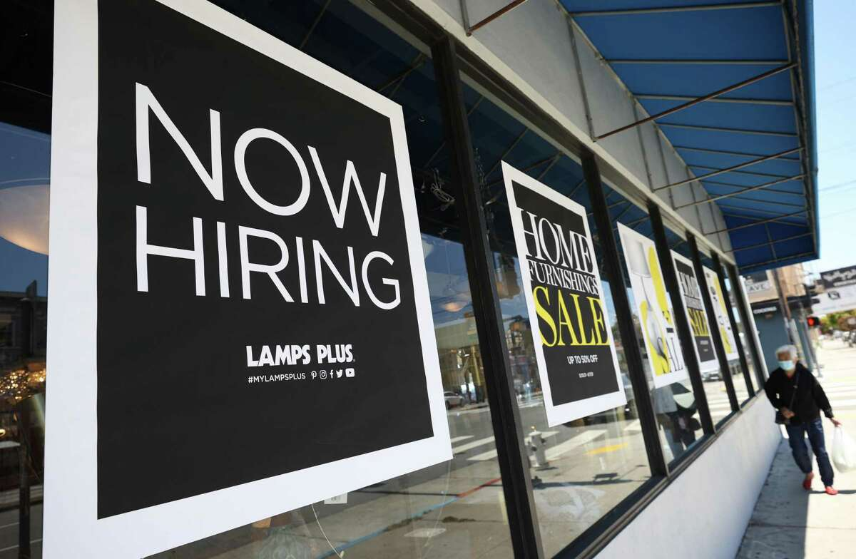 Hiring accelerated in Texas and the nation in June. A pedestrian walks by a Now Hiring sign outside of a Lamps Plus store on June 03, 2021, in San Francisco, California. (Justin Sullivan/Getty Images/TNS)