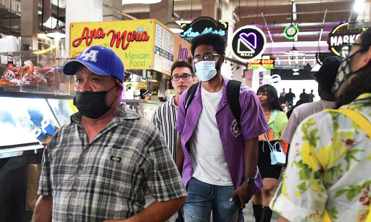 Masked and unmasked people make their way through Grand Central Market in Los Angeles in late June. Los Angeles County is again mandating masks for vaccinated as well as unvaccinated people, starting Saturday night.