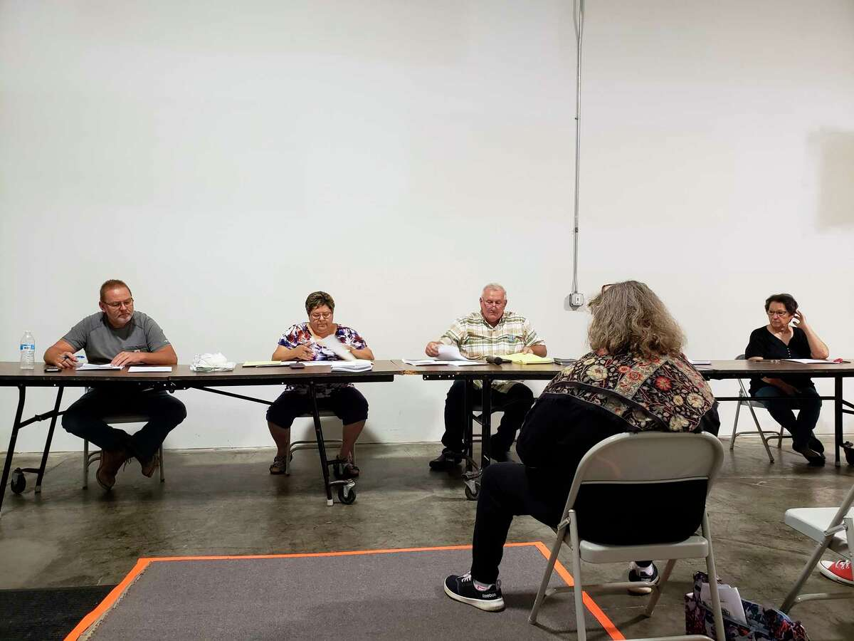 The Greenleaf Township Board of Trustees prepare fortheir meeting on Thursday evening, where they fielded questions from the audience about a long-ongoing lawsuit. The township was ordered to pay $137,000 as a result of the suit, which had been going on since 2016. (Robert Creenan/Huron Daily Tribune)