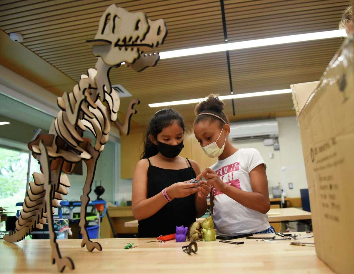 Allison Jimenez, left, and Diyanara Correa look at 3D printed objects at the Greenwich Library Innovation Lab in Greenwich, Conn. Tuesday, July 13, 2021. Students from the Greenwich-based social services nonprofit Community Centers Inc. are visiting the Innovation Lab every Tuesday as part of the CCI Summer Program. They're free to create and experiment with many advanced tools such as 3D printers, laser cutters and engravers, VHS to DVD converters, and much more.