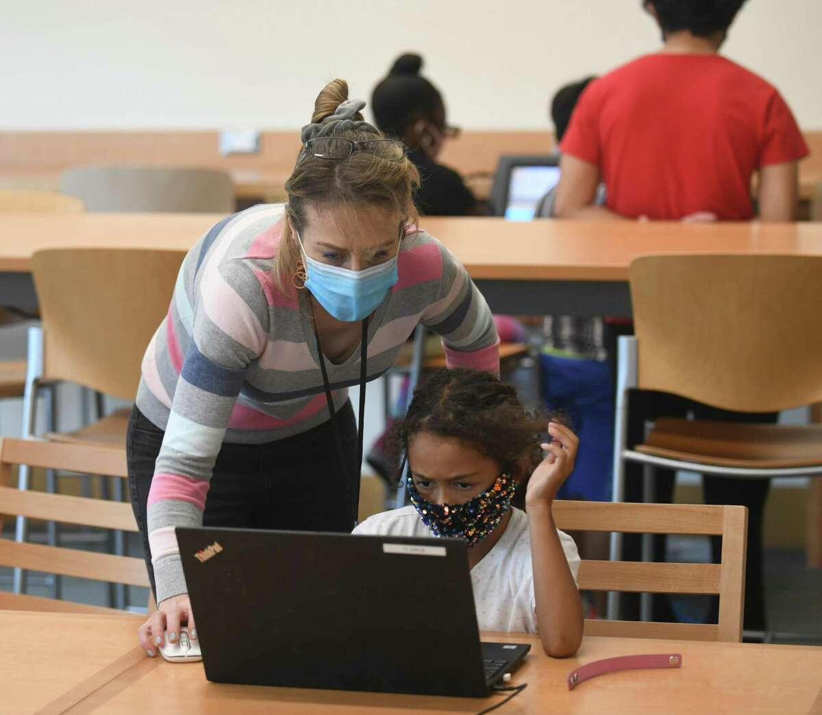 Innovation Lab Coordinator Vanessa Harrington helps Makayla Williams on the laptop at the Greenwich Library Innovation Lab in Greenwich, Conn. Tuesday, July 13, 2021. Students from the Greenwich-based social services nonprofit Community Centers Inc. are visiting the Innovation Lab every Tuesday as part of the CCI Summer Program. They're free to create and experiment with many advanced tools such as 3D printers, laser cutters and engravers, VHS to DVD converters, and much more.