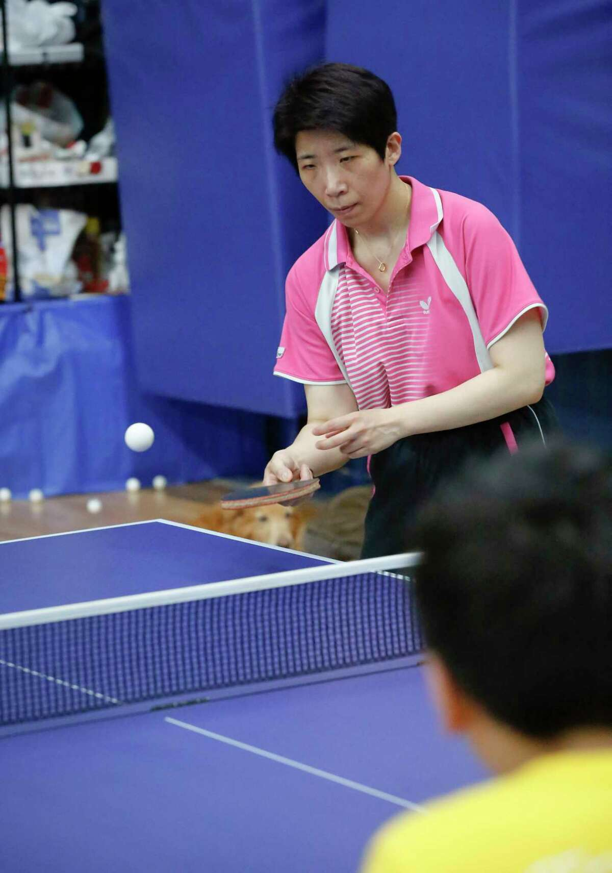 Table tennis coach Huijing Wang instructs Andrew Cao, 13, at the Houston Badminton Center, Tuesday, July 13, 2021, in Stafford.