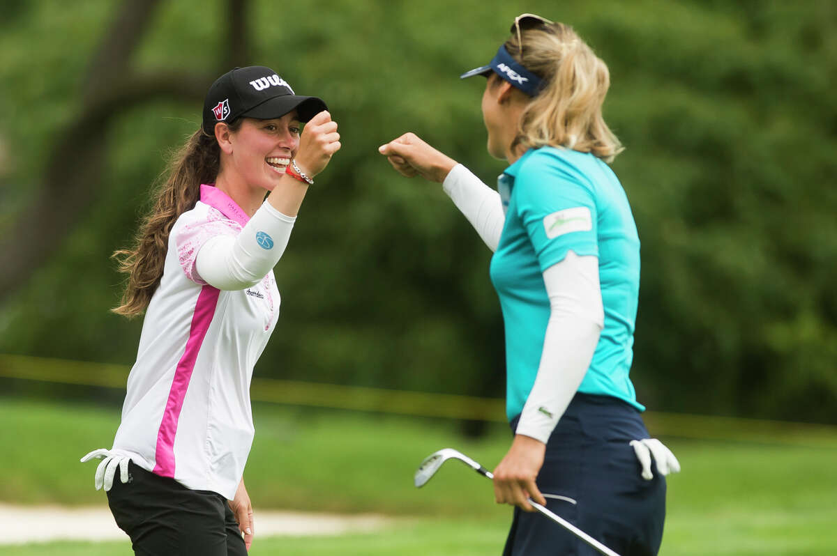 LPGA player Nuria Iturrioz, left, fist bumps her playing partner, Celine Herbin, right, as they compete in the third round of play during the Dow Great Lakes Bay Invitational Friday, July 16, 2021 at the Midland Country Club. (Katy Kildee/kkildee@mdn.net)