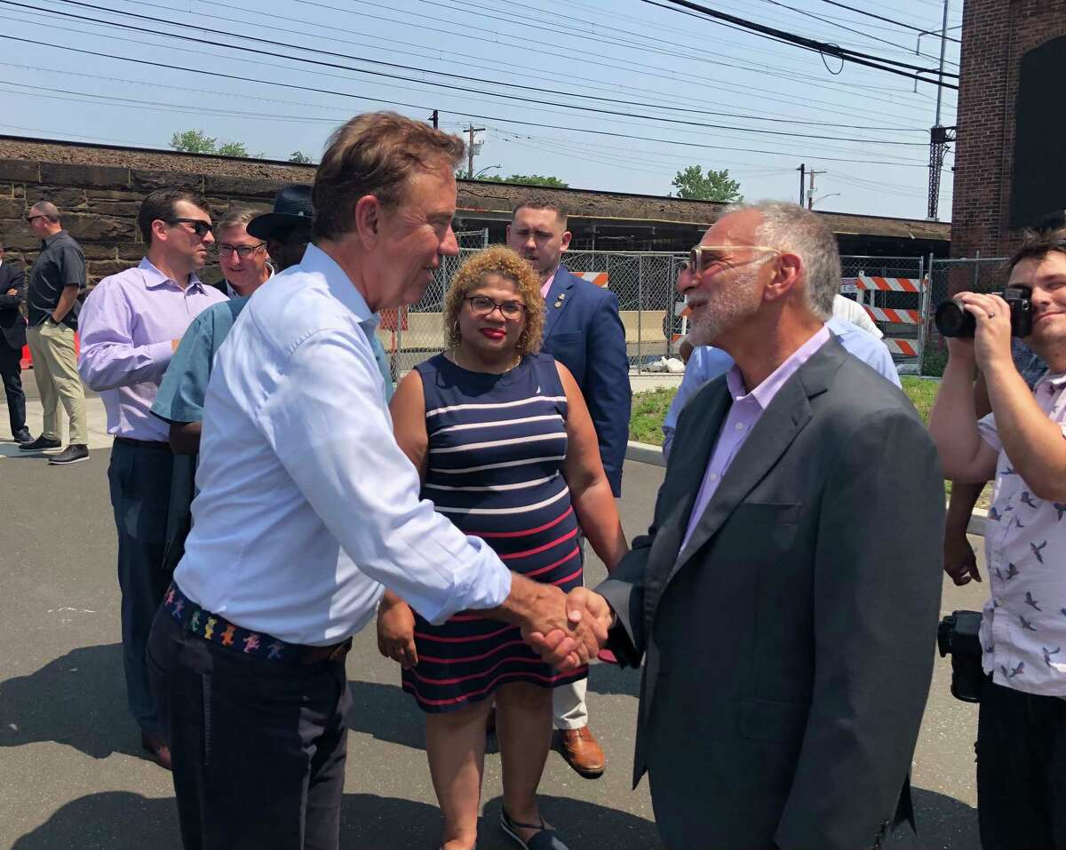 Govl Ned Lamont shakes hands with developer Gary Flocco before a groundbreaking ceremony at the Cherry Street Lofts in Bridgeport, Conn. July 16, 2021.
