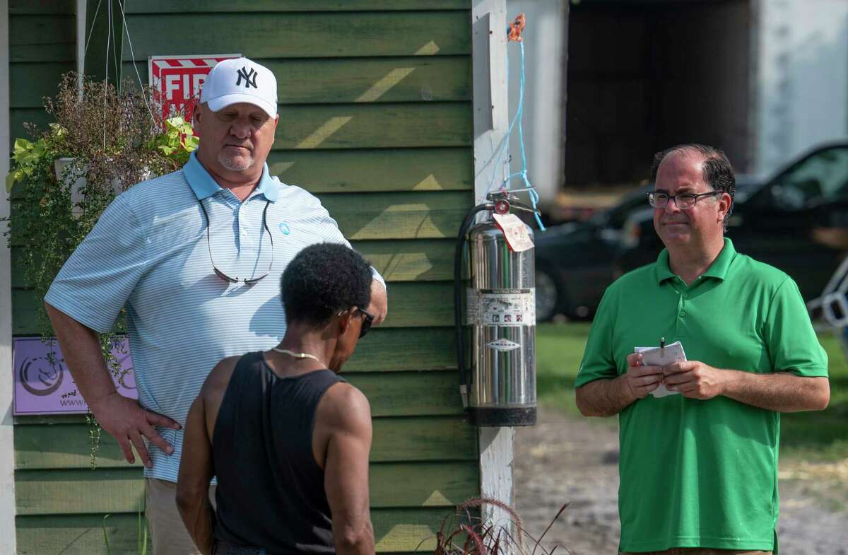 Trainer Kenny McPeek, left, speaks with his assistants after a virus was detected in a horse stabled in an adjacent barn to his at the Saratoga Race Course Friday July 16, 2021 in Saratoga Springs, N.Y. . Photo Special To the Times Union by Skip Dickstein