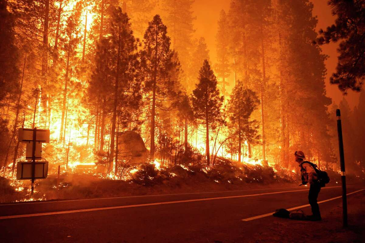 Gabe Huck (right), a member of a San Benito-Monterey Cal Fire crew, stands along state Highway 168 while fighting the Creek Fire on Sept. 6 in Shaver Lake (Fresno County).