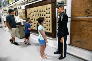 From left, Timothy Funtak of North Branford tours the West Haven Veterans Museum and Learning Center with his children Caden, 7, and Lilliana, 9, on July 15, 2021. Lilliana is looking at a U.S. Army dress blue infantry uniform from 1902 on a mannequin. Funtak and his son are viewing an 1893 Connecticut National Guard Roster.