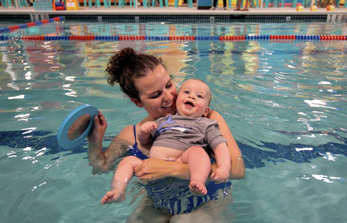 Lauren Prince plays in the pool with her10 month old son Nathan at Goldfish Swim School in Stamford, Conn., on Wednesday July 14, 2021. The school opened in May and offers swim lessons to infants and children.