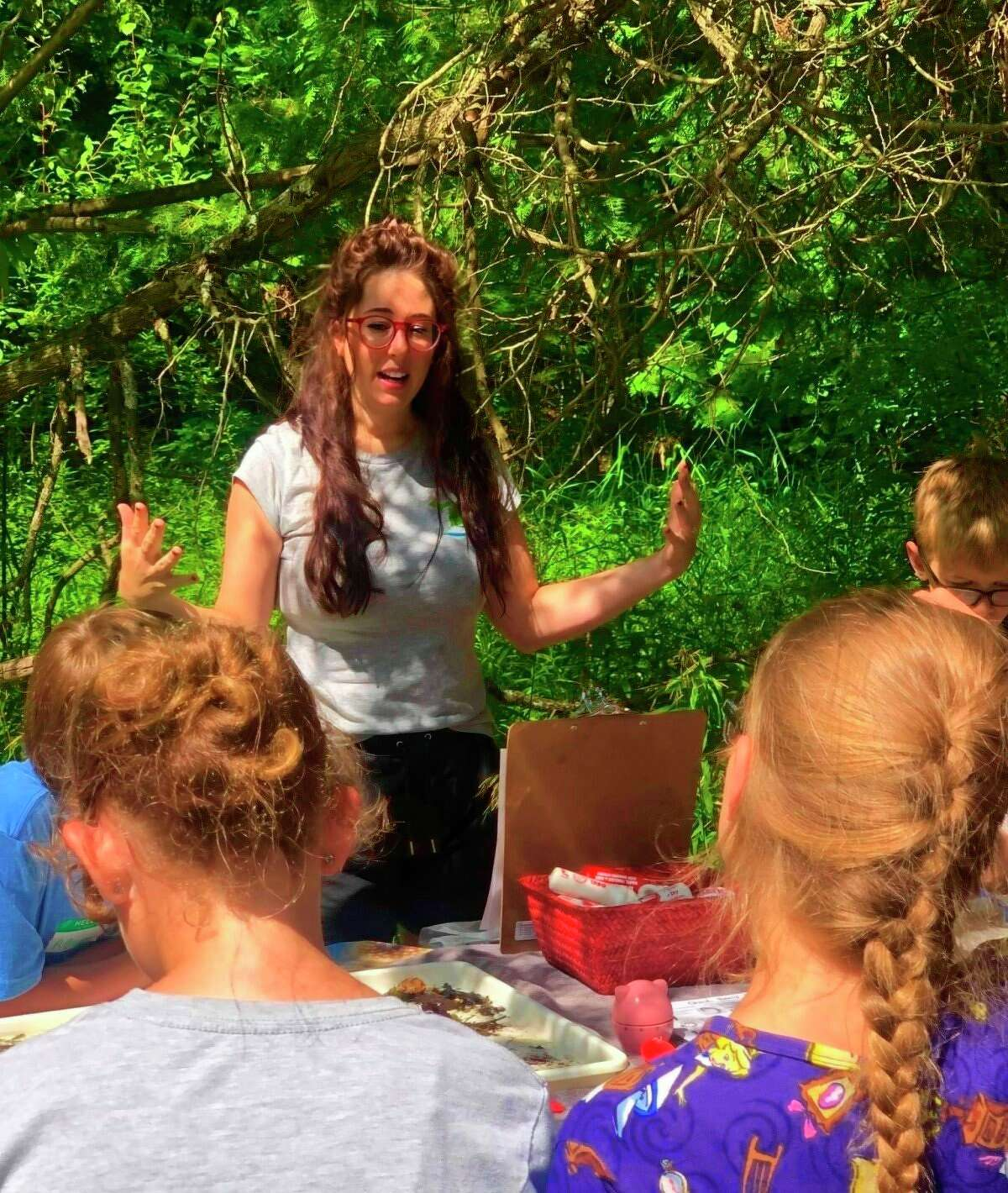 ChelseaCooper,Manistee Conservation District conservation technician and aquatic invasive species outreach coordinator, teaches kids aboutaquatic macroinvertebrates and invasive species at theSpirit of the Woods Conservation Club's free youth camp on Tuesday. (Courtesy photo)