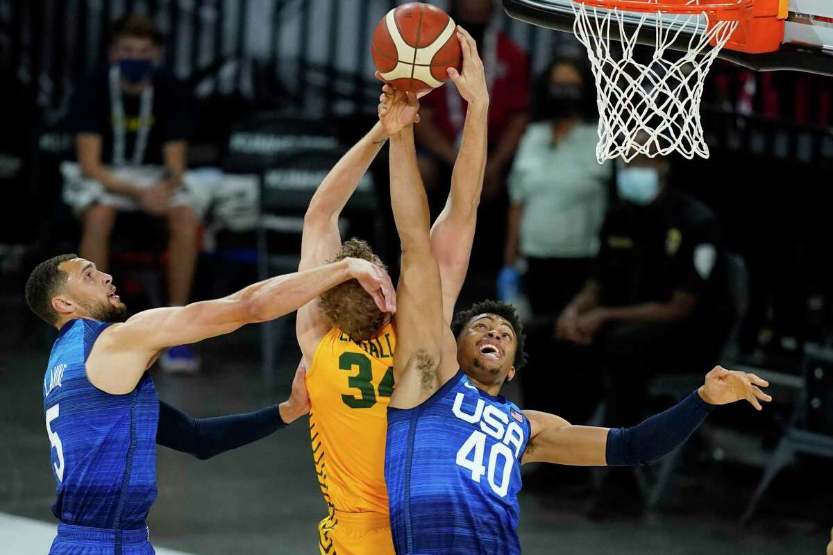 United States' Zach LaVine, left, and Keldon Johnson, right, battle for a rebound with Australia's Jock Landale during an exhibition basketball game Monday, July 12, 2021, in Las Vegas. (AP Photo/John Locher)