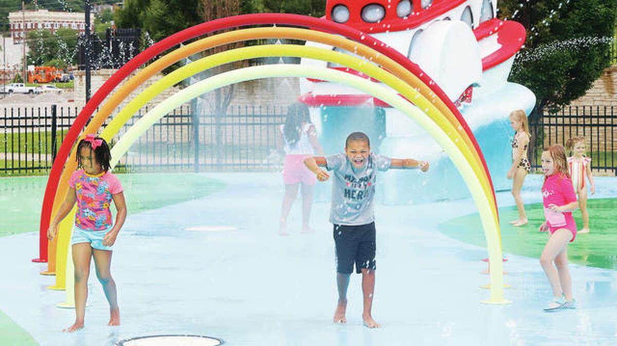 Kids run through a rainbow-like arch that sprays water Friday at the new Alton Splash Pad.