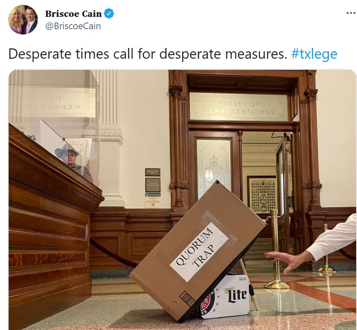"""State Rep. Briscoe Cain tweeted a photo of a case of Miller Lite underneath a cardboard box labeled """"Quorum Trap."""" The box is held up with a stick and a hand is reaching for the case of beer."""