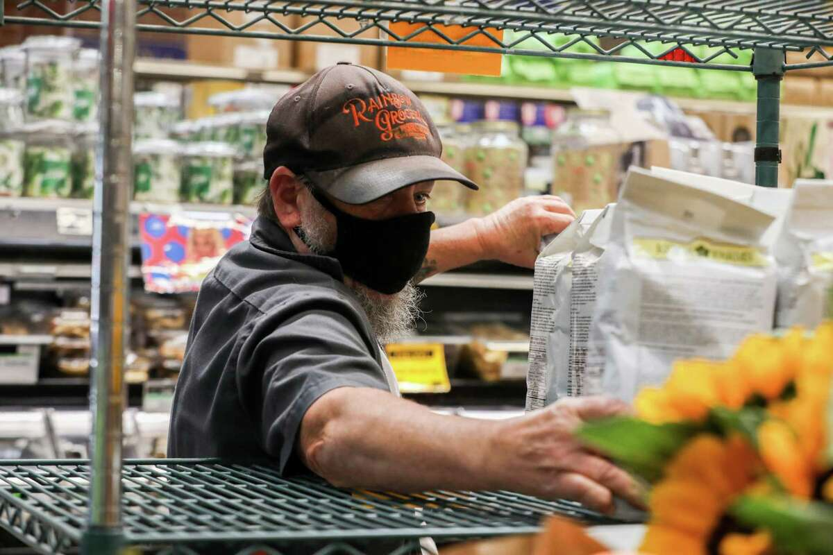 A Rainbow Grocery employee stocks a shelf with pancake mix in San Francisco in June. Masks are required in indoor public settings in San Francisco.