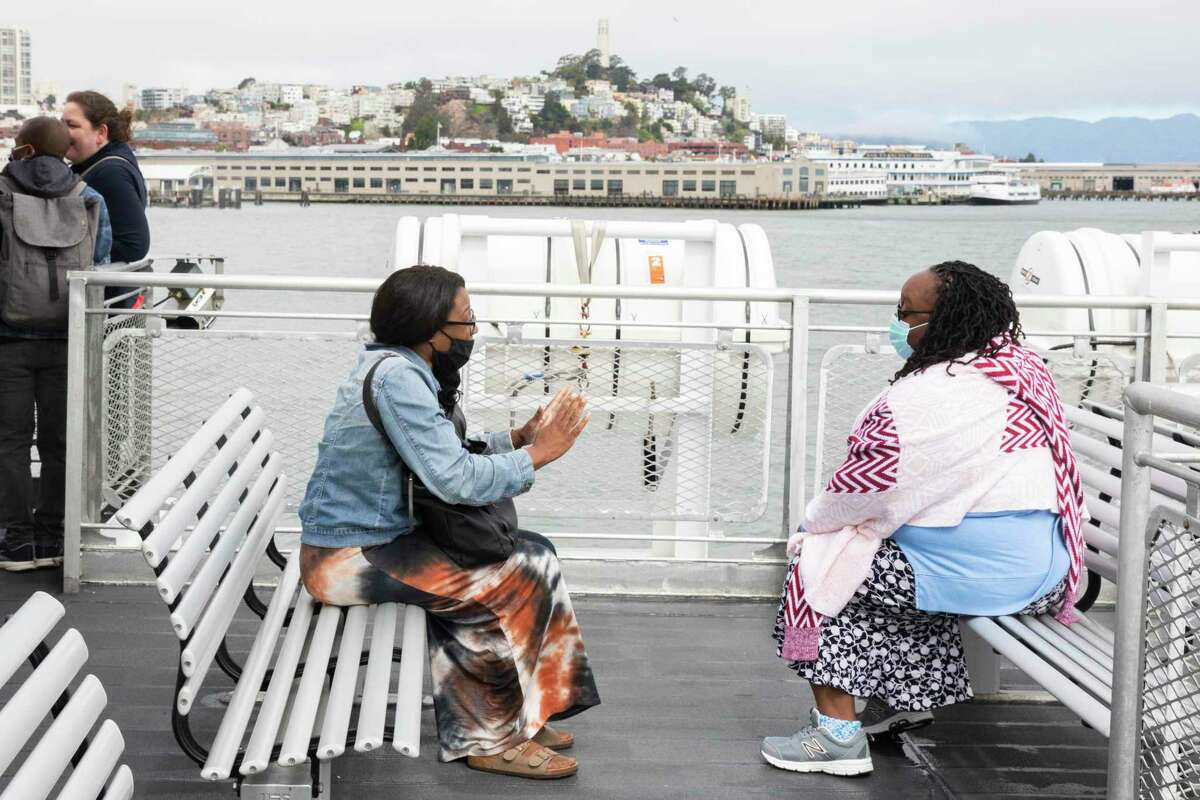 Jeanette Archie of Sacramento (left) and Lyndale Garner of Sacramento wear masks as they chat while riding the the San Francisco-bound ferry boat from Vallejo on Tuesday, July 6.