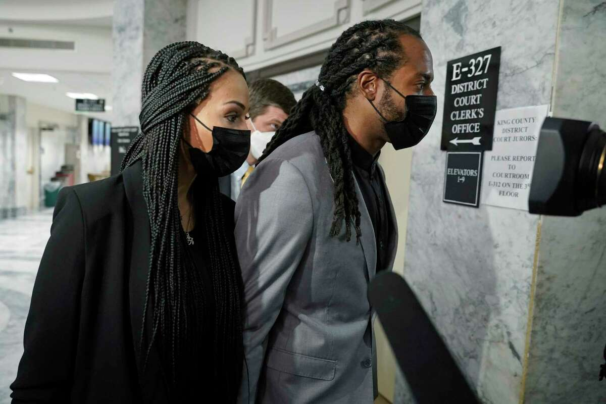 Richard Sherman, right, walks with his wife Ashley, Friday, July 16, 2021, following a King County District Court hearing in Seattle. The NFL football cornerback, who has played with the Seattle Seahawks and the San Francisco 49ers, was arraigned on five criminal charges Friday after he was arrested Wednesday after police said he crashed his car in a construction zone along a busy highway east of Seattle and then tried to break into his in-laws' home in the suburb of Redmond, Wash.