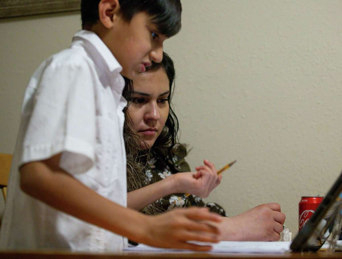 Vanessa Rodriguez, center, helps her 9-year-old son Giovanny with math home work after eating dinner in their home Wednesday, Feb. 3, 2021, in Crosby, Texas. Rodriguez, from Mexico, has been thinking about applying for DACA for many years, but it wasn't until president Joe Biden took office that she finally felt safe to do so. As a mother of three American children, she was afraid of giving her information to the government and being deported. Now she and her husband are among the many DACA eligible people that are applying for the first time.