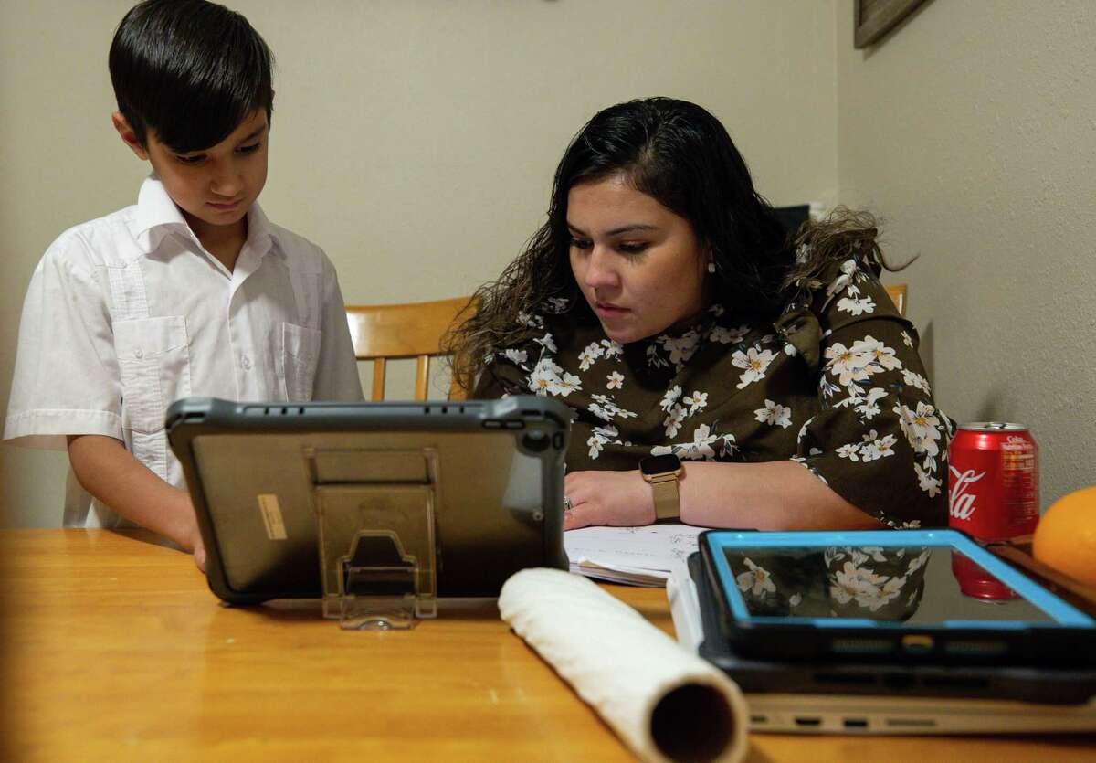 Vanessa Rodriguez, right, helps her 9-year-old son Giovanny with math home work after eating dinner in their home Wednesday, Feb. 3, 2021, in Crosby, Texas. Rodriguez, from Mexico, has been thinking about applying for DACA for many years, but it wasn't until president Joe Biden took office that she finally felt safe to do so. As a mother of three American children, she was afraid of giving her information to the government and being deported. Now she and her husband are among the many DACA eligible people that are applying for the first time.