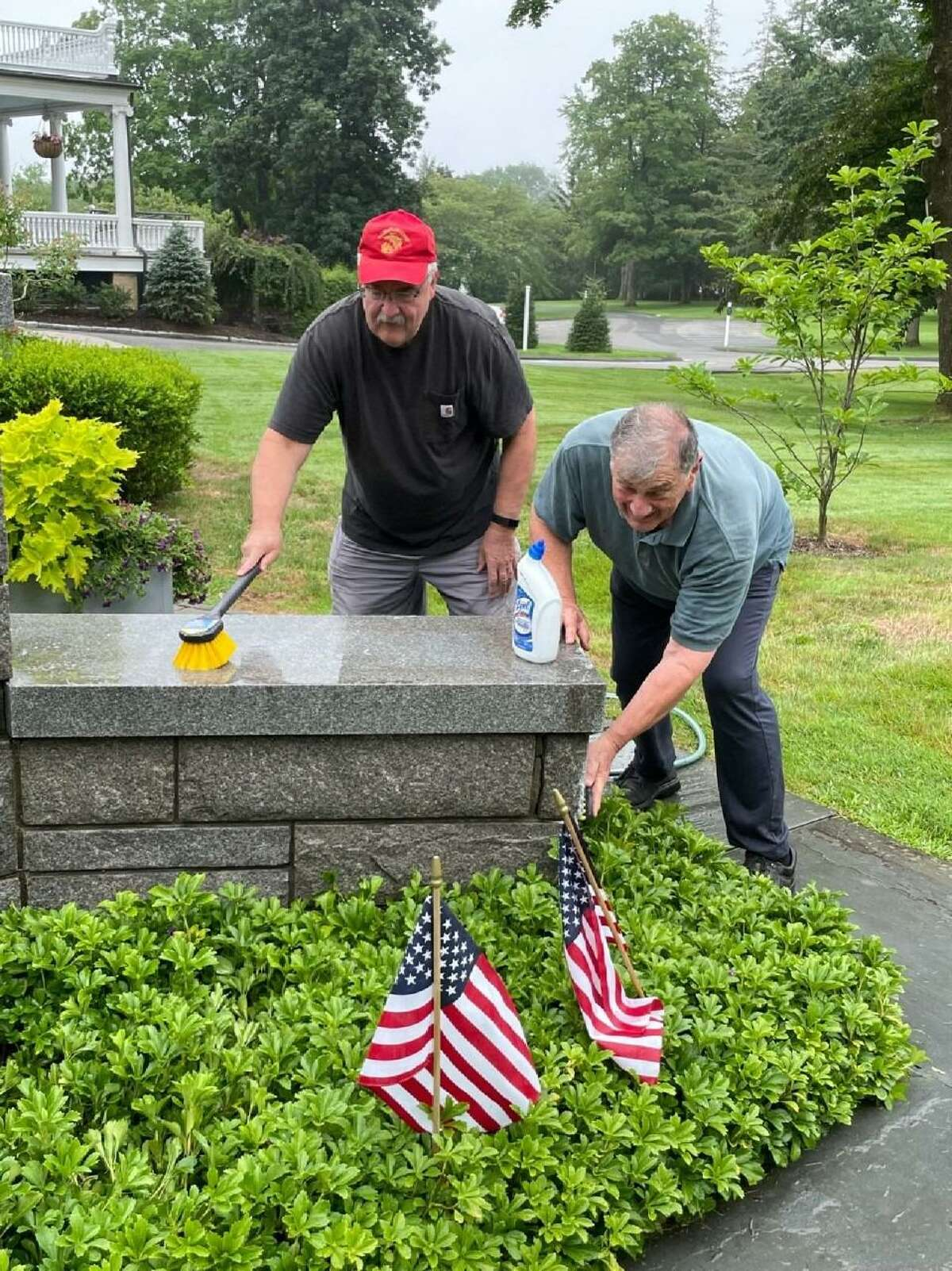 Marine Corps veterans Pete Killie, left, and Dick Tiani, scrub down the Veterans Memorial Monument at Lounsbury House in Ridgefield. The historic mansion has supported veterans since it opened to visitors in 1954.