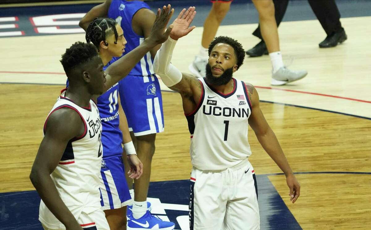 Nov 25, 2020; Storrs, CT, USA; Connecticut Huskies guard R.J. Cole (1) celebrates with forward Adama Sanogo (left) after a play against the Central Connecticut State Blue Devils in the second half at Gampel Pavilion. Mandatory Credit: David Butler II-USA TODAY Sports
