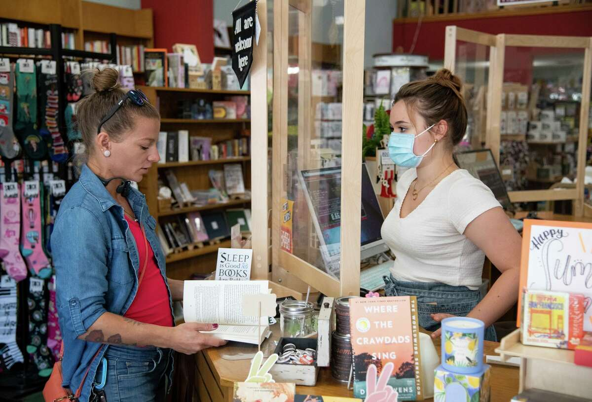 Marinka Swift, left, buys a book from Sophia Fingerman, right, at Avid Reader Bookstore in Davis on Friday. Yolo County is one of nine California counties that is recommending everyone wear masks indoors again. Avid Reader Bookstore's staff continues to wear masks.