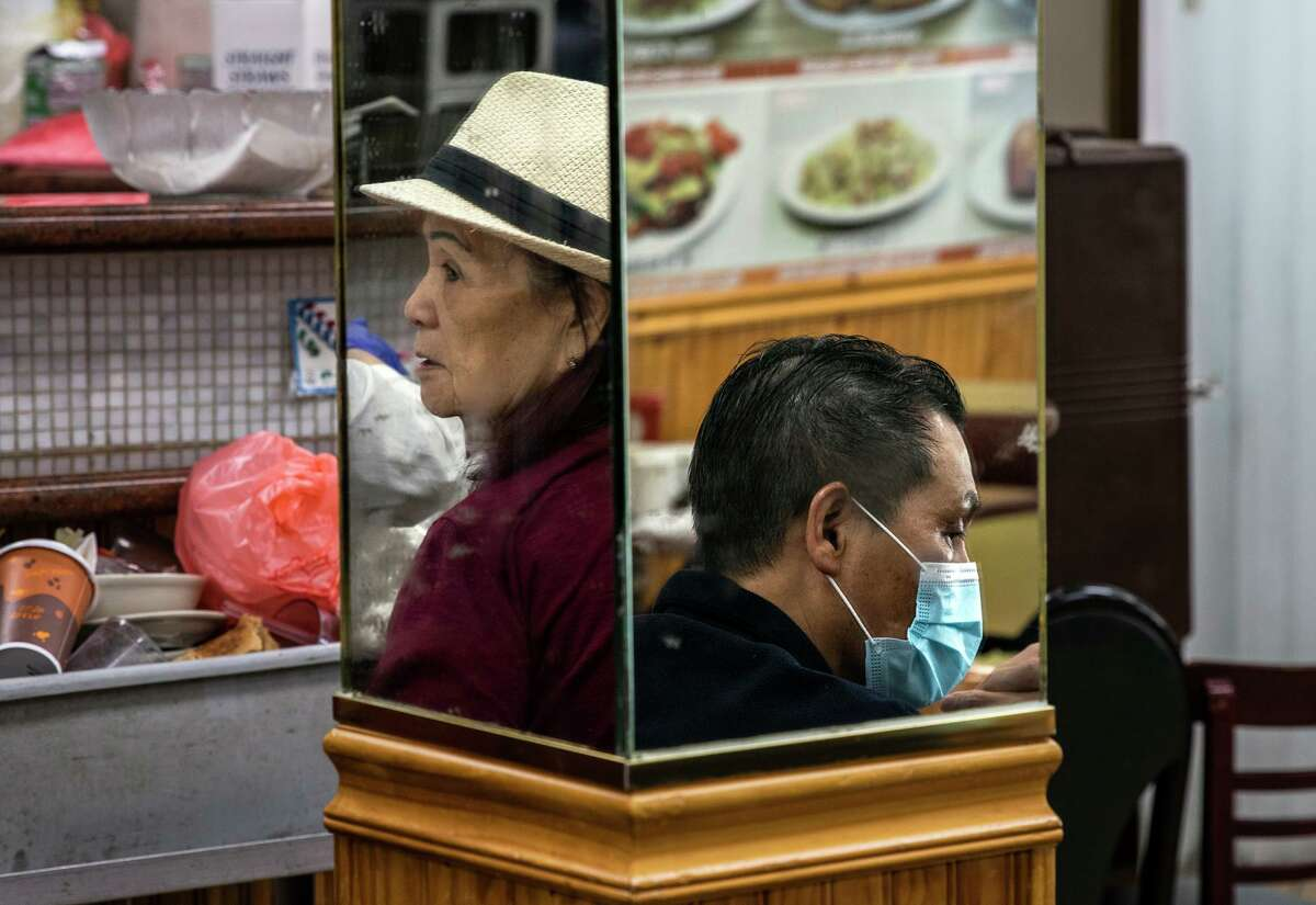 Customers are reflected in mirrors in VIP Cafe in San Francisco's Chinatown. Many people have continued to wear masks.