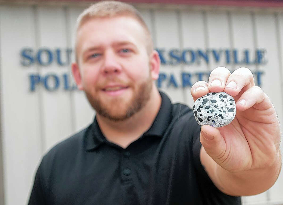 South Jacksonville Police patrolman Hunter Parks holds up his custom-painted, cow-themed rock that he bought from Alaina Shillings, 7, while on patrol Tuesday evening.