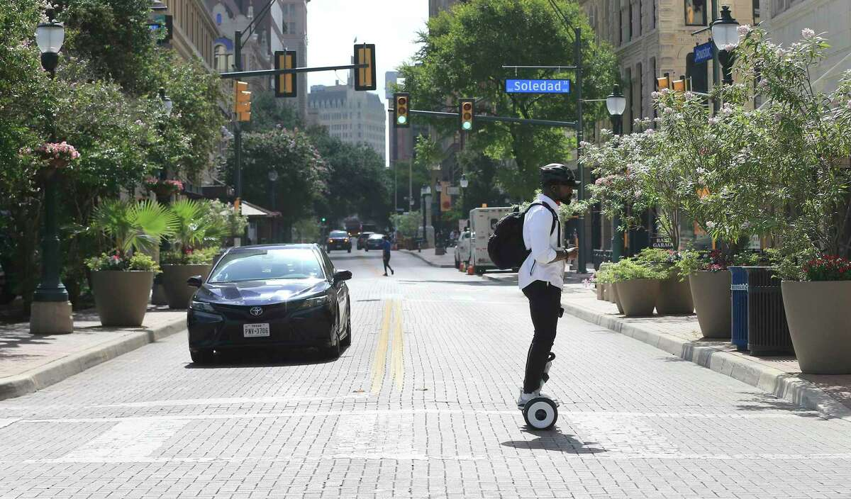 Terry French, founder and CEO of social networking company WXYZr, rides across Houston Street on a hoverbot.