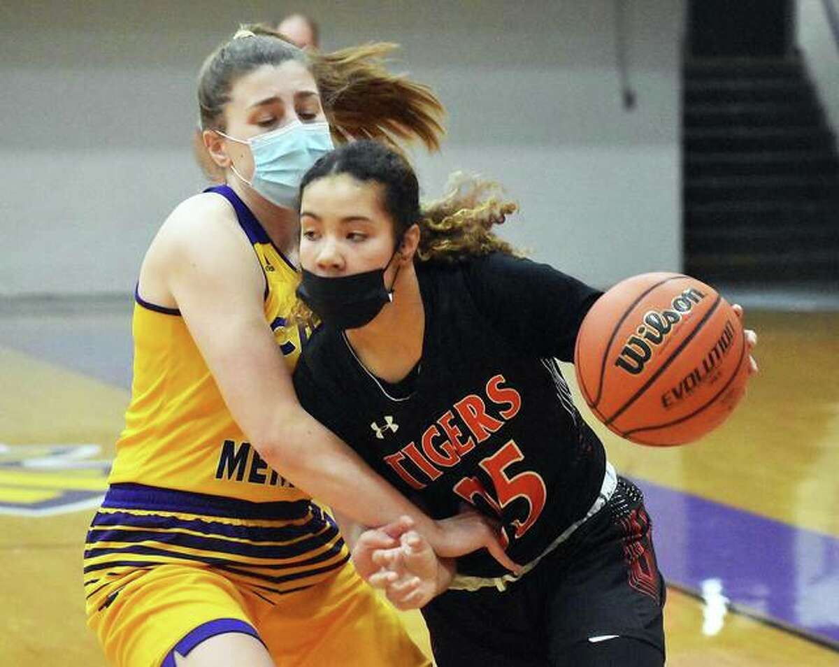 Edwardsville junior Sydney Harris (right) drives past Civic Memorial's Jackie Woelfel during a Tigers win Feb. 12 in Bethalto. Harris averaged 19.8 points a game for the 16-1 Tigers to earn 2021 Telegraph Large-Schools Girls Basketball Player of the Year honors.