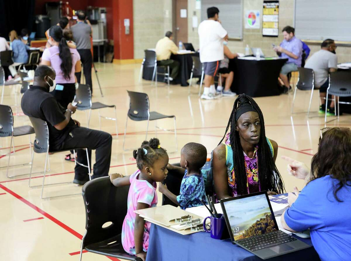 Kristal Jones, center, and two of her children Kamaiyah and Malik get help to fill out the application for the Emergency Rental Assistance program at the Baker Ripley Gulfton-Sharpstown campus on Friday, July 16, 2021, in Houston. As the federal moratorium on evictions expires at the end of the month, tenants and landlords are encouraged to apply to this program as there are still funds. Harris County has allocated approximately $137 million to 36,000 households and the U.S. Department of Treasury has announced an additional $21.55 billion in emergency rental assistance for families across the country; roughly $53 million will be added to the Houston-County program, with more funding expected in the coming months.