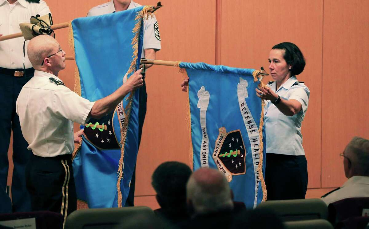 Lt. Gen. Ronald J. Place (left), director of Defense Health Agency and Brig. Gen. Jeannine M. Ryder (right), commander of the 59th Medical Wing and Market Director unveil the new San Antonio Market flags during a ceremony as military officials at Brooke Army Medical Center announce changes to the San Antonio Military Health System renamed San Antonio Market on Friday, July 16, 2021. The system services about 250,000 beneficiaries throughout the area providing health care to those in the military.