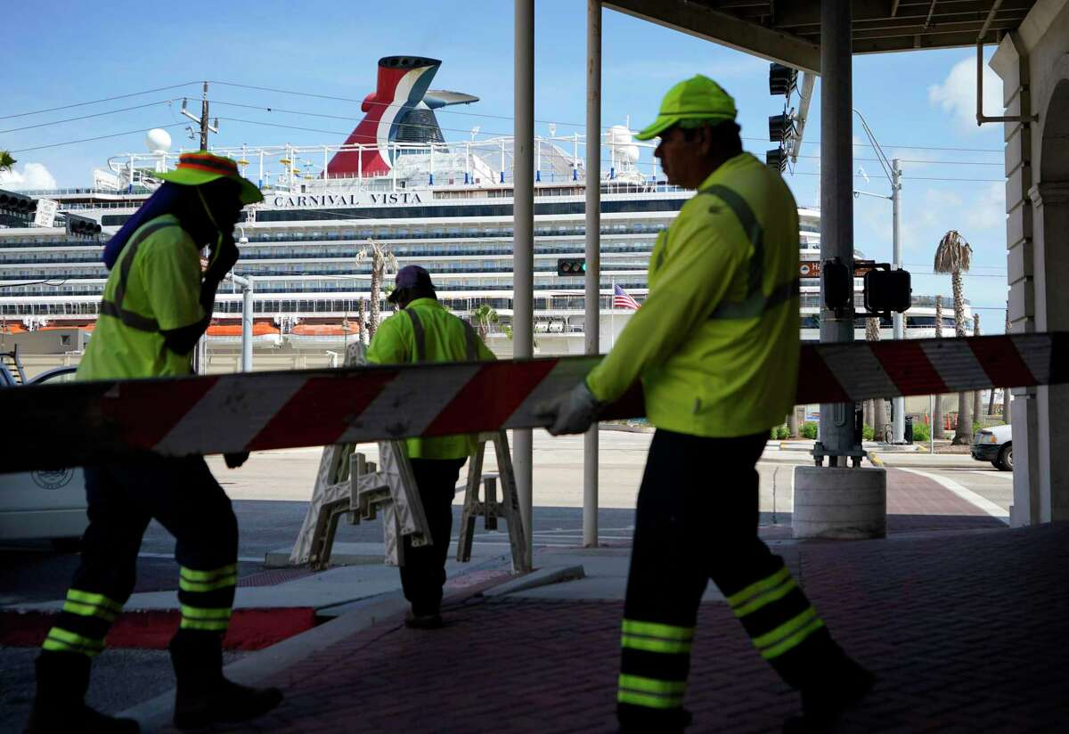 The Carnival Vista, shown as city crews gather barricades for the Fourth of July parade, is the first cruise to sail out of Galveston since the pandemic began, thanks to an exception in state law.