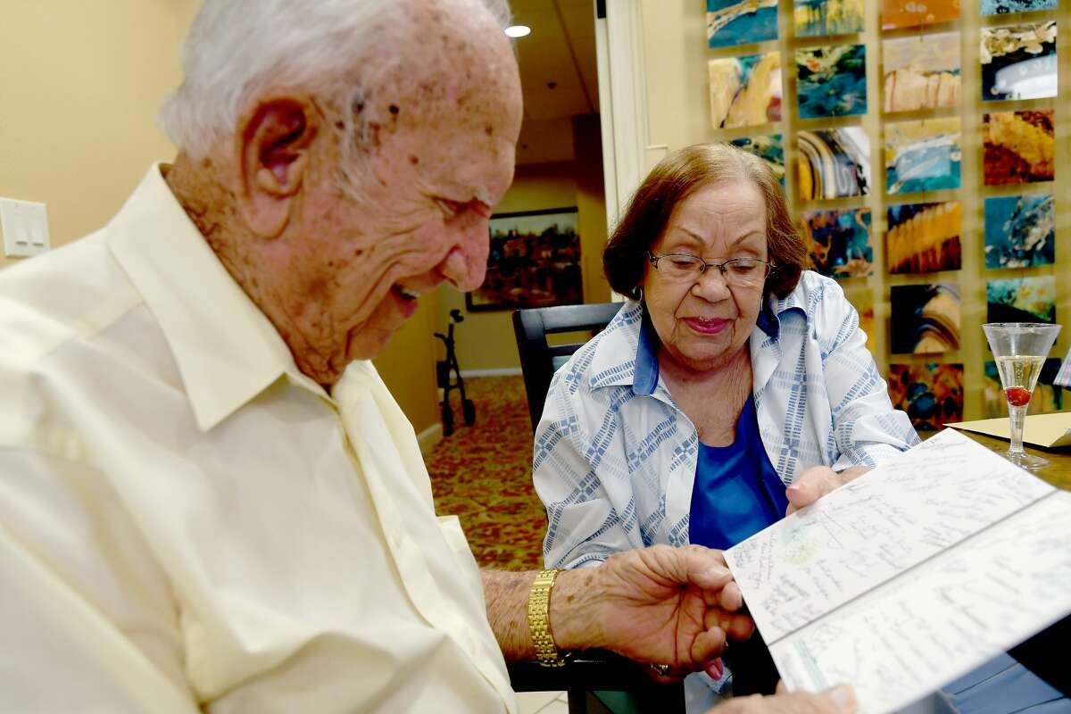 Johnnie and Bill Grantham read through a card during a 76th wedding anniversary celebration held for them at Calder Woods Friday. Generations of their family, including great-grandchildren they haven't seen in two years due to the pandemic, joined with staff and friends for the party. Photo made Friday, July 16, 2021 Kim Brent/The Enterprise