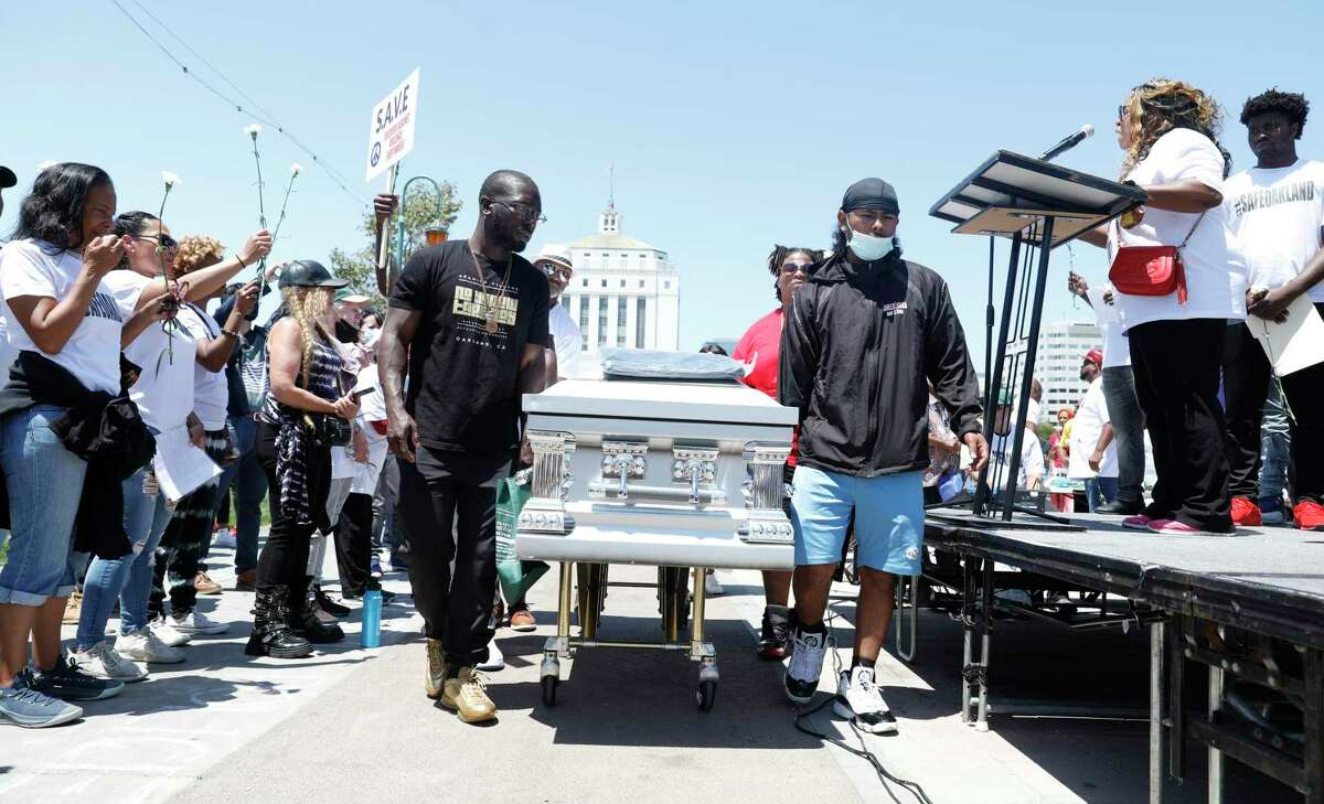 """At the """"Stand Up For A Safe Oakland"""" anti-violence rally on July 10, some attendees carry a coffin to represent people killed by gun violence in the city. Numerous attendees spoke to the crowd about the lives of loved ones cut short by gun violence."""