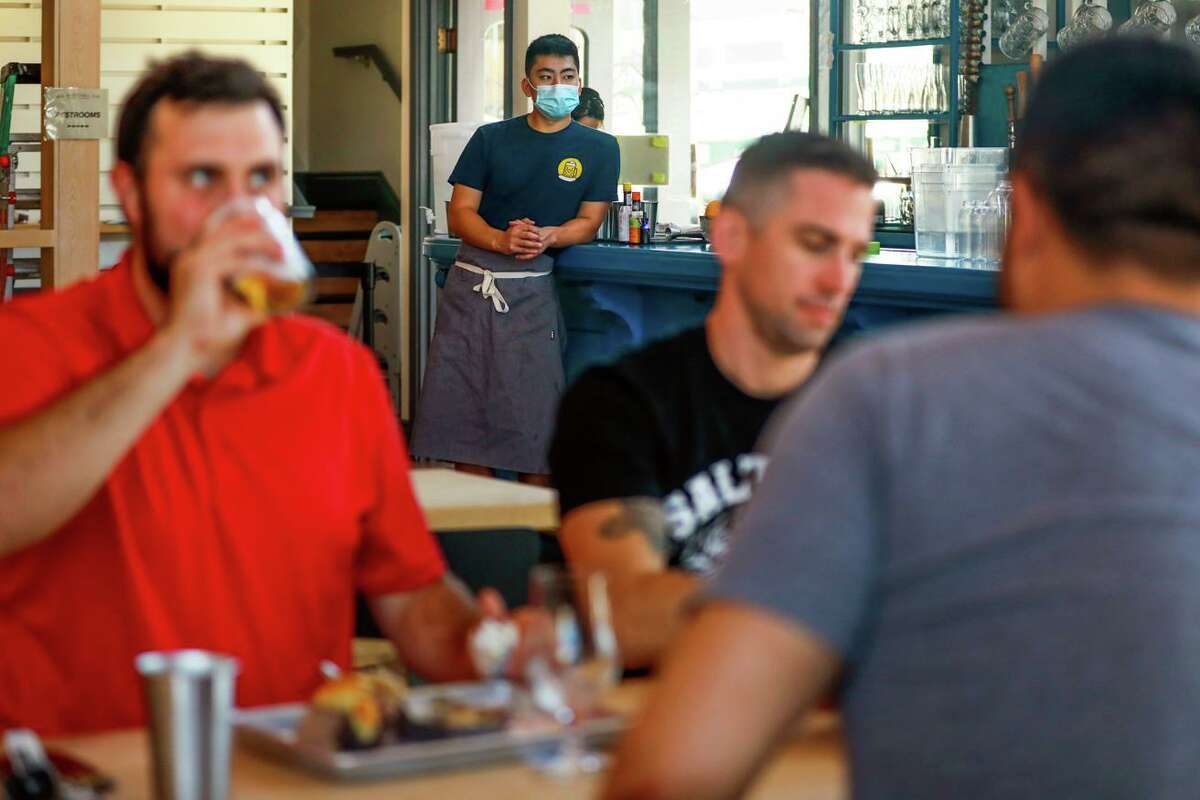 """Server Brett Kuwahara (second from left) wears a mask as he stands near diners Jake """"JaCandy"""" Andriola (left), David Betty, (center) and Ryan Pozivenec (right) at Wursthall on Friday, July 16, 2021 in San Mateo, California. Restaurants were scrambling on Friday to respond to a new public health recommendation in seven Bay Area counties that vaccinated people again wear masks indoors."""