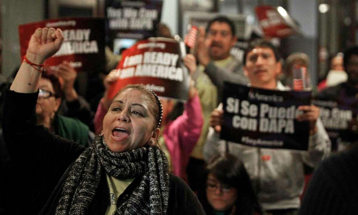 En esta fotografía de archivo del martes 17 de febrero de 2015, Mercedes Herrera y otras personas corean consignas durante un evento sobre los programas DACA y DAPA en el Centro Internacional de Comercio de Houston, Texas.