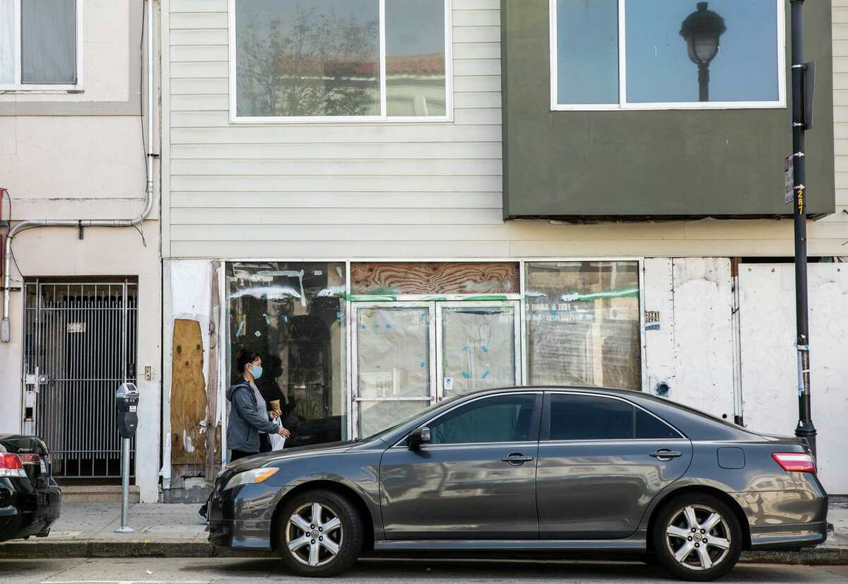 A pedestrian walks by the unfinished section of an illegal building along San Bruno Avenue in the Portola District of San Francisco. Originally approved for ten units, the developer built nearly 30.