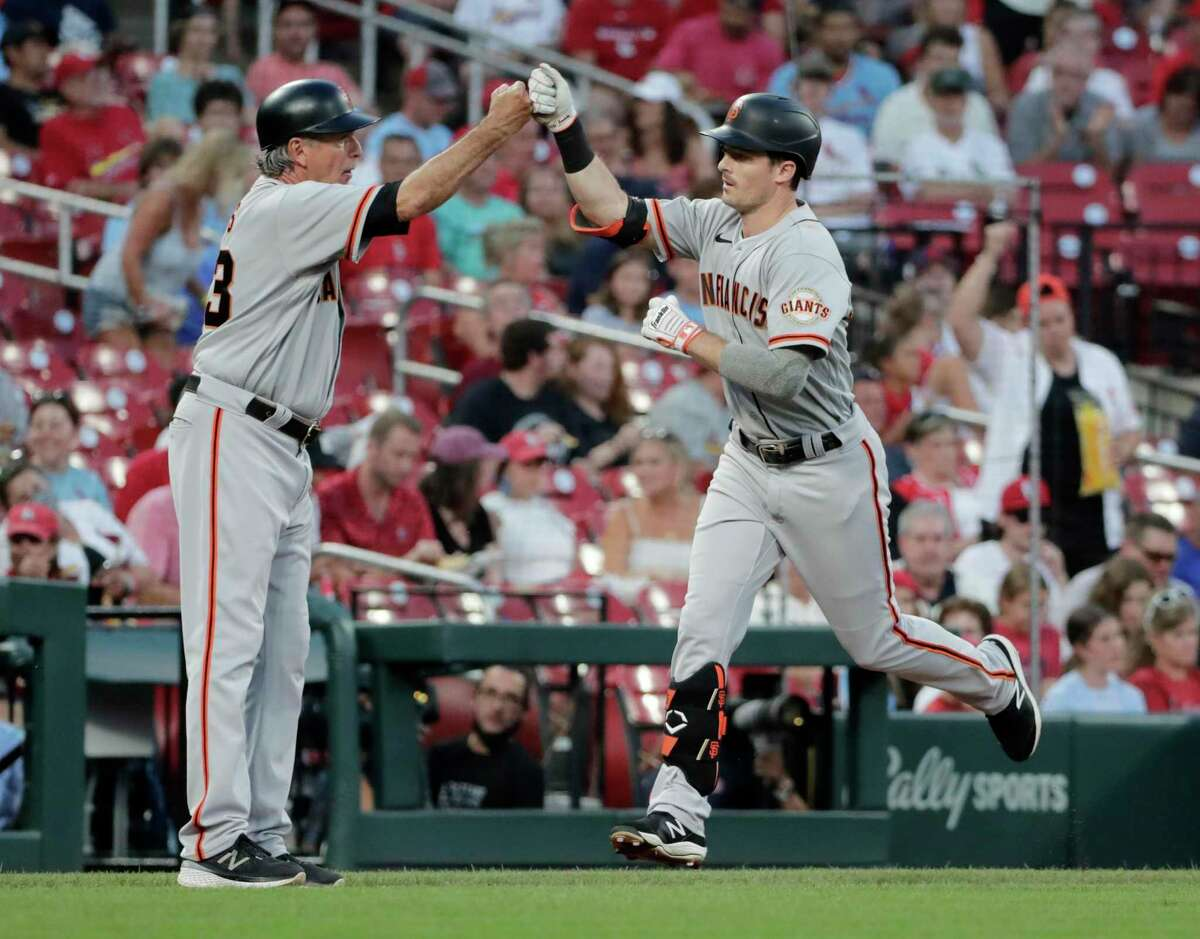 San Francisco Giants' Mike Yastrzemski (5) celebrates with third base coach Ron Wotus (23) after hitting a solo home run in the fourth inning of a baseball game against the St. Louis Cardinals, Friday, July 16, 2021, in St. Louis. (AP Photo/Tom Gannam)