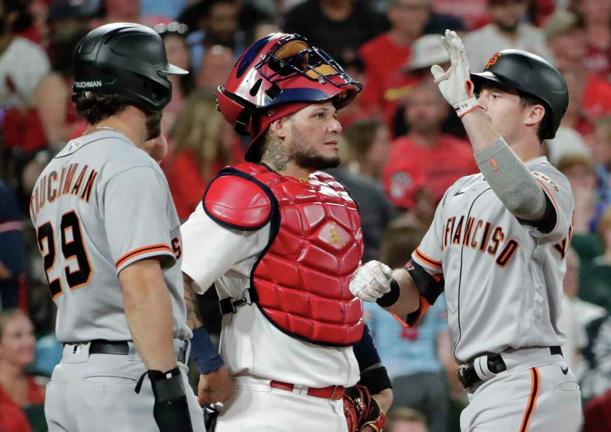San Francisco Giants' Mike Yastrzemski, right, celebrates with teammate Mike Tauchman after hitting a three-run home run, as St. Louis Cardinals catcher Yadier Molina (4) watches the replay in the seventh inning of a baseball game, Friday, July 16, 2021, in St. Louis. (AP Photo/Tom Gannam)