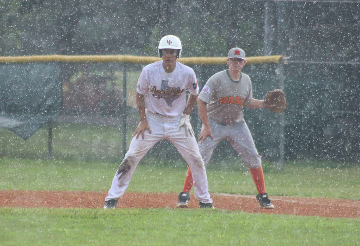 In the pouring rain Friday morning at Bay Area Park, Deer Park's Gabe Salinas gets a lead off first base after hitting a two-RBI single in the NASA contest. Moments later, the umpiring crew ordered the players off the field.