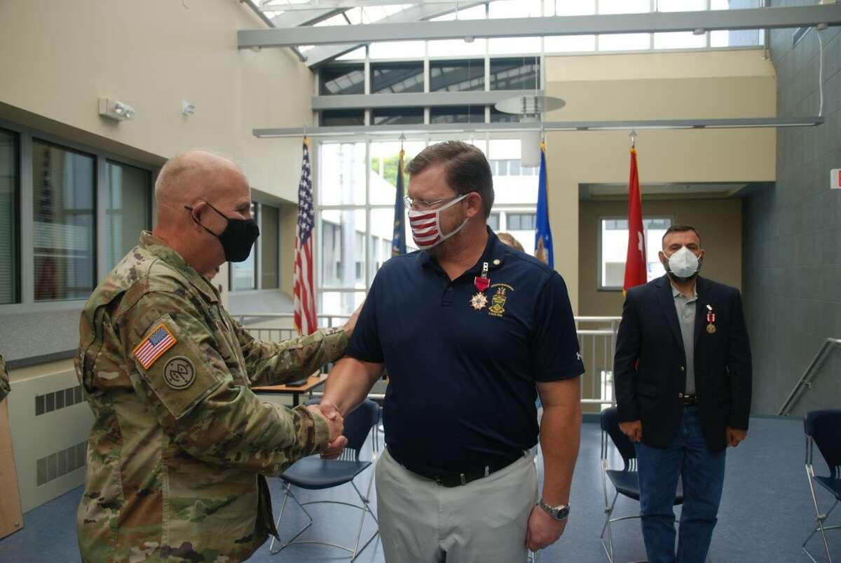 Ret. Sgt. Maj. Matthew Gutzwiller, right, is congratulated by Maj. Gen. Raymond Shields, after Gutzwiller received a Legion of Merit Medal during a ceremony in Latham.