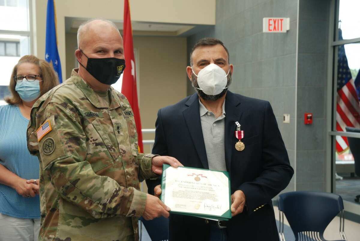 Ret. Sgt. 1st Class Frank DeThomasis, right, receives Meritorious Service Medal citation from Maj. Gen. Raymond Shields. That citation represents his second award of a Meritorious Service Medal.