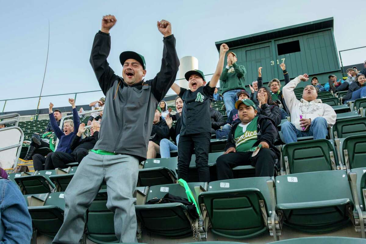 From left: Michael Ramirez, with his son, Michael Leovardo Ramirez Jr., 10, and their neighbor's son, Marvin Carranza Castellanos, 7, react as the Oakland Athletics score against the Cleveland Indians on Friday.