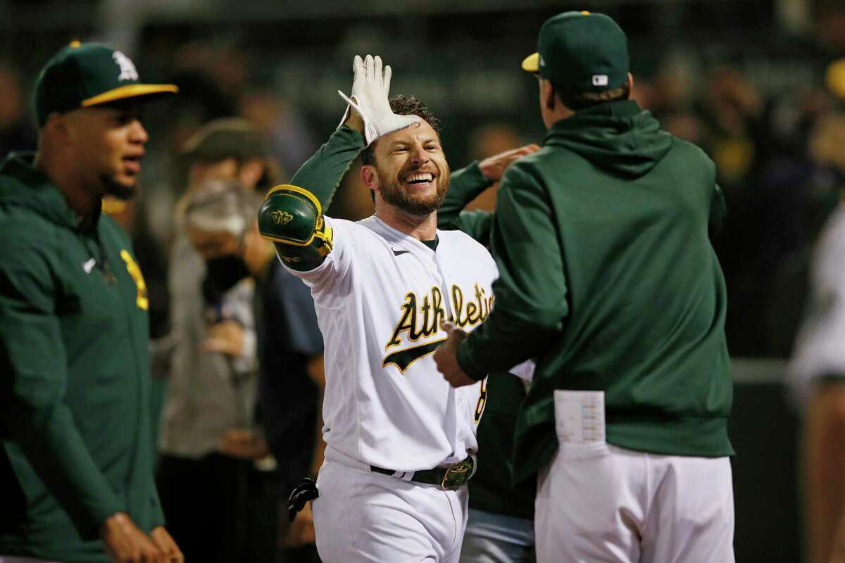 Oakland Athletics Jed Lowrie (8) celebrates his two-run walk-off homer in the ninth inning during an MLB game against the Cleveland Indians at RingCentral Coliseum, Friday, July 16, 2021, in Oakland, Calif. The A's won 5-4.