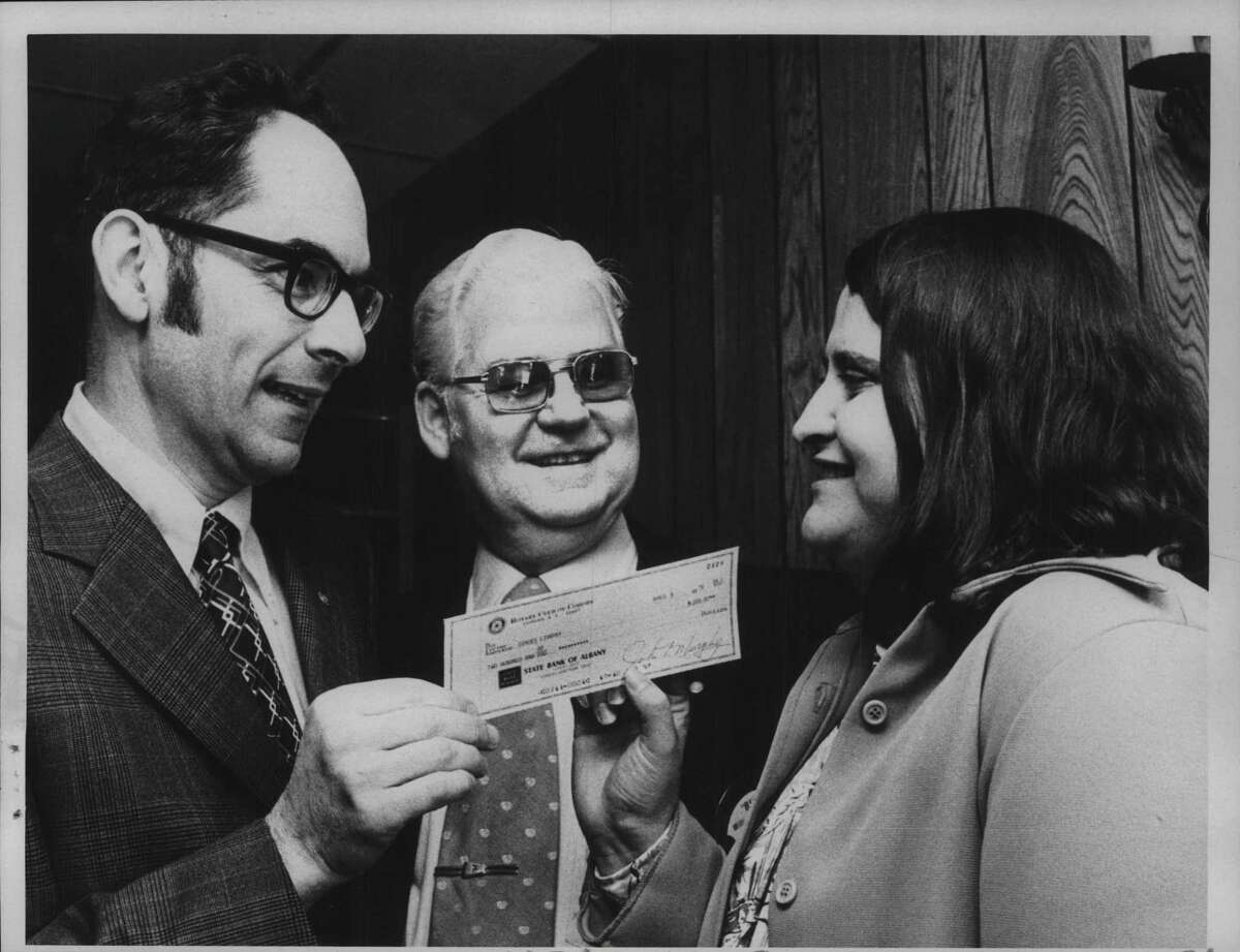 (From left) R. Mihran Mooradian, President of Cohoes Rotary Club, William J Dillon, program chair, and Carol Clingan, chief librarian at Cohoes Public Library, receives check for $200 from the Cohoes Rotary Club at dinner at Mac's Restaurant in Cohoes, New York. April 17, 1975 (Bob Richey/Times Union Archive)