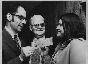 R. Myron Mooradian, President of Cohoes Rotary Club, William J Dillon, program chair, and Carol Clingan, chief librarian at Cohoes Public Library, receives check for $200 from the Cohoes Rotary Club at dinner at Mac's Restaurant in Cohoes, New York. April 17, 1975 (Bob Richey/Times Union Archive)