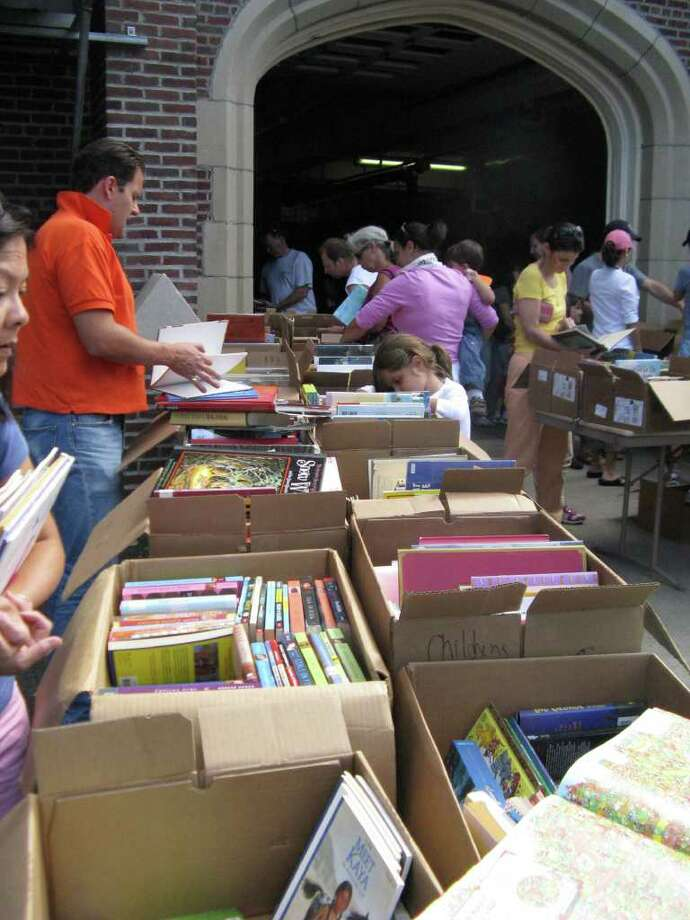 Leafing through one of the used books at the Cos Cob Library Book Sale was Tim Zawislack, left. Though he works in e-commerce he says he still likes the book-in-the-hand. Photo: Anne W. Semmes / Greenwich Citizen